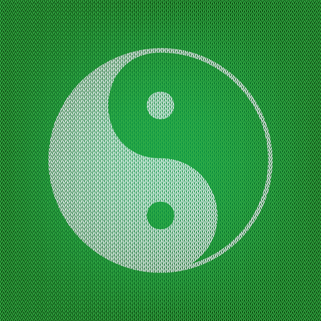 Ying yang symbol of harmony and balance. white icon on the green knitwear or woolen cloth texture.
