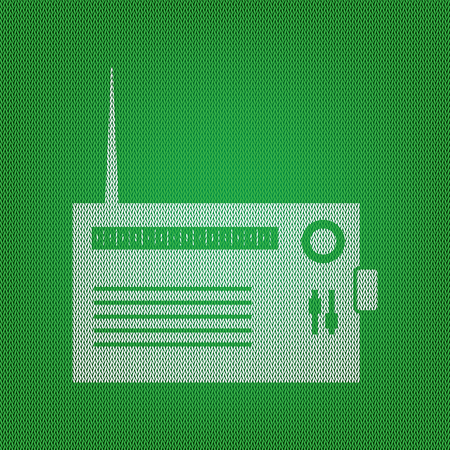 volume knob: Radio sign illustration. white icon on the green knitwear or woolen cloth texture.