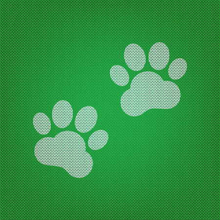 Animal Tracks sign. white icon on the green knitwear or woolen cloth texture.