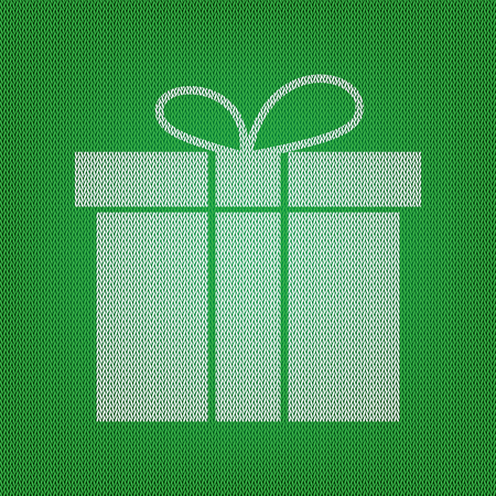 Gift box sign. white icon on the green knitwear or woolen cloth texture.