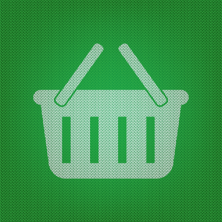 Shopping basket sign. white icon on the green knitwear or woolen cloth texture.