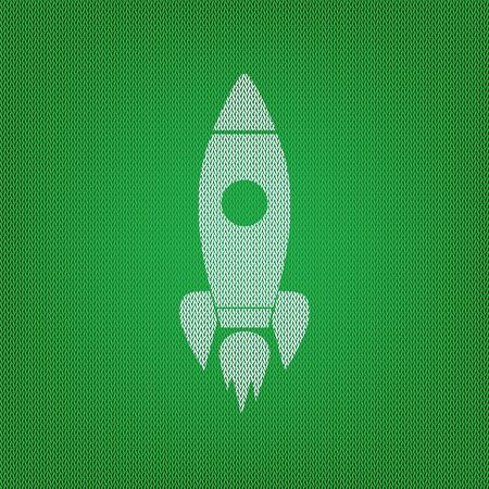 Rocket sign illustration. white icon on the green knitwear or woolen cloth texture.