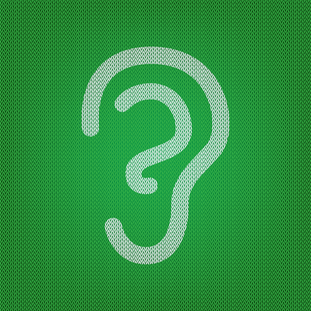 Human ear sign. white icon on the green knitwear or woolen cloth texture.