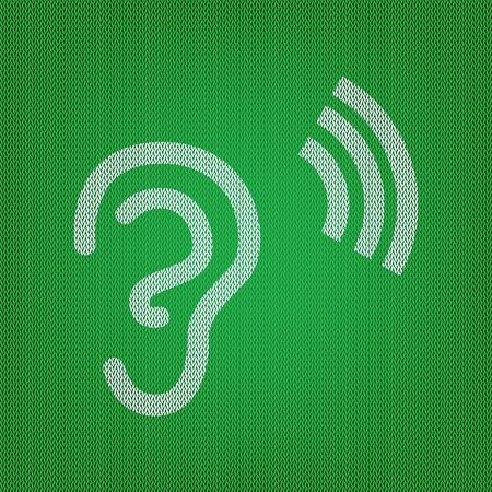 audible: Human ear sign. white icon on the green knitwear or woolen cloth texture.