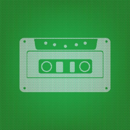 Cassette icon, audio tape sign. white icon on the green knitwear or woolen cloth texture. Illustration