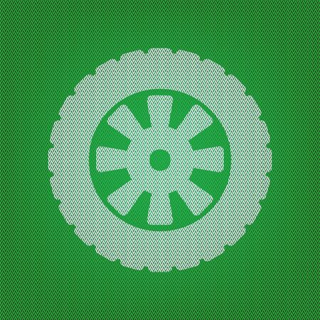 Road tire sign. white icon on the green knitwear or woolen cloth texture.