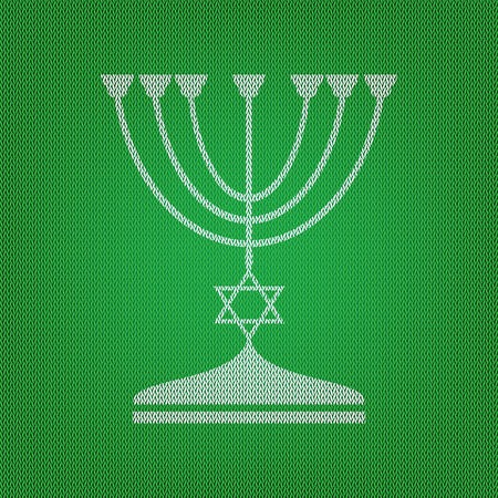 Jewish Menorah candlestick in black silhouette. white icon on the green knitwear or woolen cloth texture.