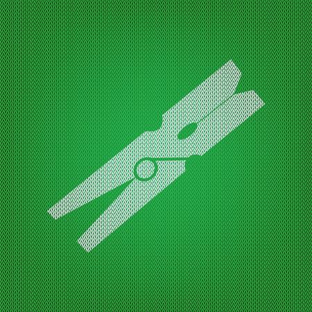 Clothes peg signe. icône blanche sur le tricot vert ou de la texture de tissu de laine.