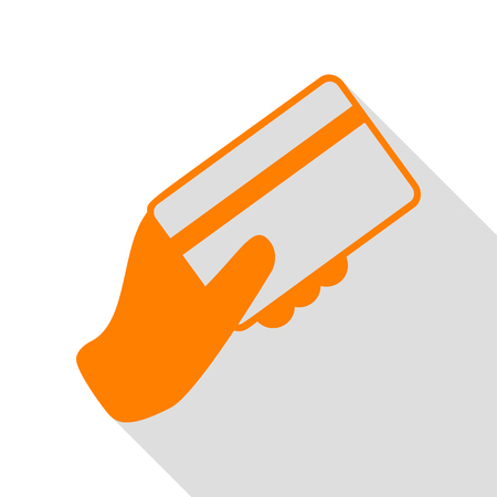 Hand holding a credit card. Orange icon with flat style shadow path.