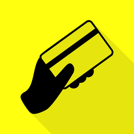 Hand holding a credit card. Black icon with flat style shadow path on yellow background.