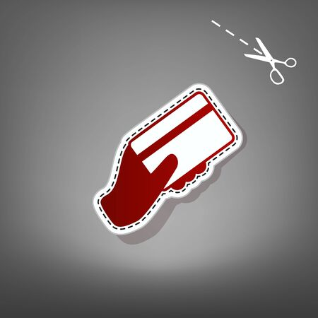 Hand holding a credit card. Vector. Red icon with for applique from paper with shadow on gray background with scissors.