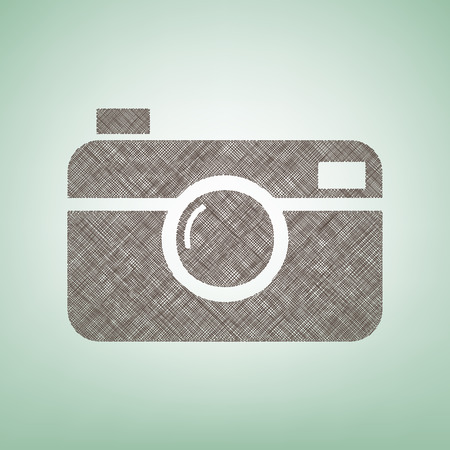 Digital photo camera sign. Vector. Brown flax icon on green background with light spot at the center.