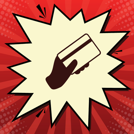 Hand holding a credit card. Vector. Dark red icon in lemon chiffon shutter bubble at red popart background with rays.