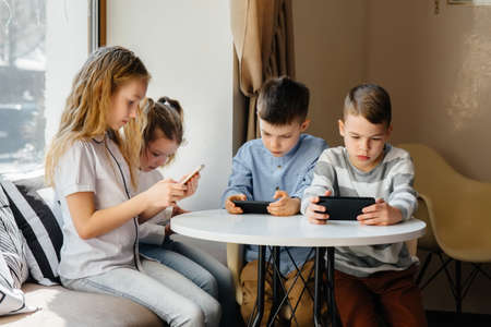 Children sit at a table in a cafe and play mobile phones together. Modern entertainment