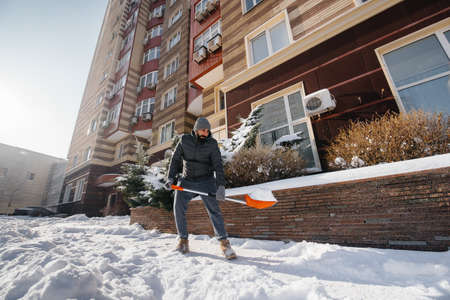 A young man clears the snow in front of the house on a sunny and frosty day. Cleaning the street from snow. 版權商用圖片