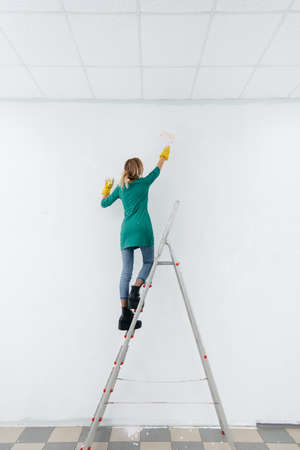 A young girl on a stepladder paints a white wall with a roller. Repair of the interior.