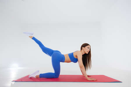 Sexy young girl performs sports exercises on a white background. Fitness, healthy lifestyle