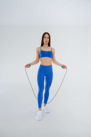 Sexy young girl jumping rope in a blue tracksuit on a white background. Fitness, healthy lifestyle