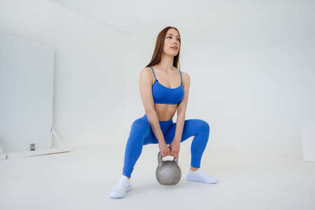 Sexy young girl exercises with a weight in a blue tracksuit on a white background. Fitness, healthy lifestyle