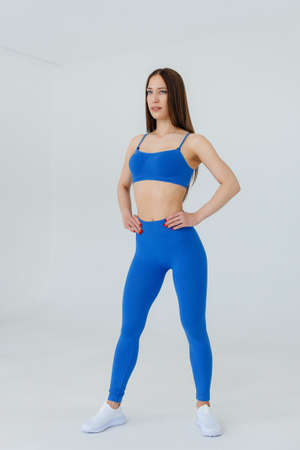 Sexy young girl posing in a blue tracksuit on a white background. Fitness, healthy lifestyle
