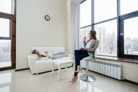 A young girl during depression communicates with a psychologist in the office. Psychological help. Banque d'images