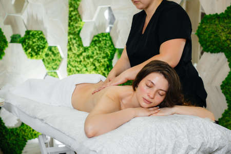 A young pretty girl is enjoying a professional cosmetological massage at the Spa. Body care. Beauty salon Stock Photo