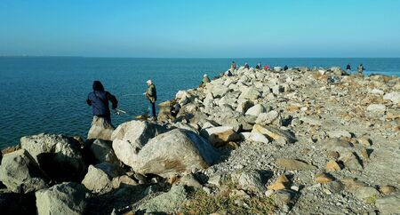 on a sunny autumn day, many anglers among the large stones of the Yeisk Spit fish in the Sea of Azov