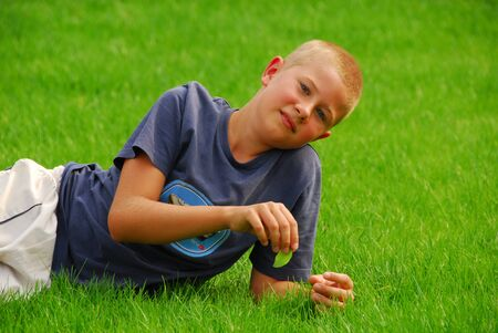 Cute little teenboy rest on a grass Stock Photo - 1504484