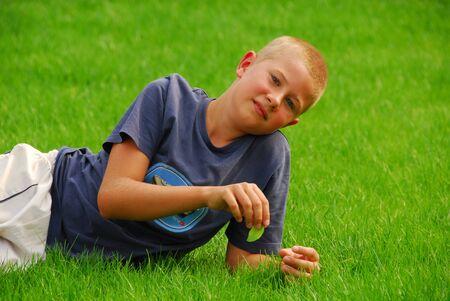 Cute teenboy peu de repos sur une herbe