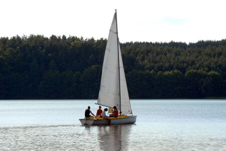 yachtsman: sailboat on the water with forest in the background