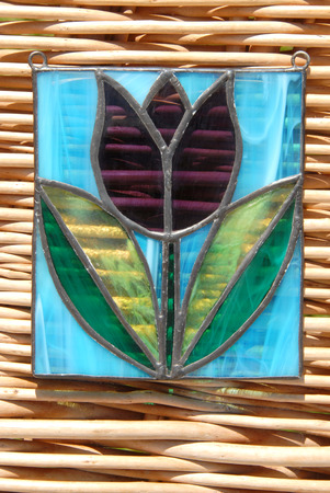 Stained glass vitrage with colourful glass in my hand on the background of wicker photo