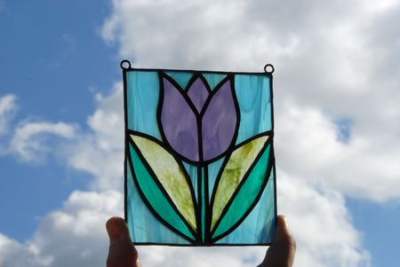 Stained glass vitrage with colourful glass in my hand on the background of sky photo
