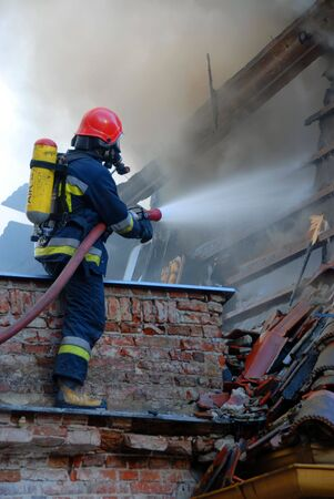 house on fire: Firemen on a roof during a house fire. Stock Photo