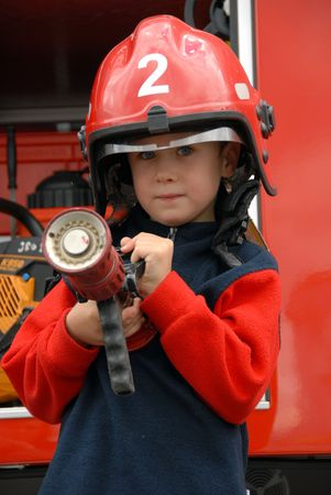 engine fire: A young boy sitting in a fire truck Stock Photo