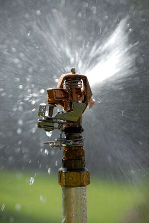 grassplot: Watering machine pouring grass-plot by water drops Stock Photo
