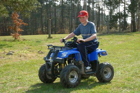 childchood: Young boy is riding four-wheeler ATV.