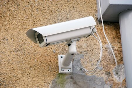 oversee: Closeup of a white generic security camera on the wall.