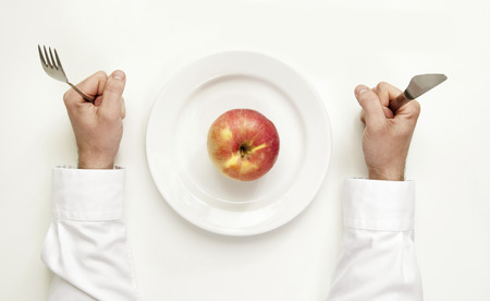 Only one apple for dinner. Diet concept. Male hands holding cutlery between plate with an apple. photo