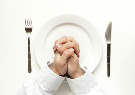Hunger concept. Man praying for food over white plate isolated on white. photo