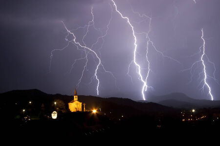 Night storm above a little chapel. Many lightning on the night sky. photo