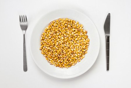 basic food: Basic food concept. Plate of dry corn with fork and knife isolated on white from top view. Stock Photo