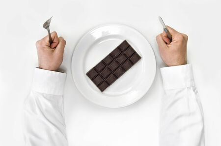 Chocolate bar on a plate and man holding fork and knife isolated on white from top view.  photo