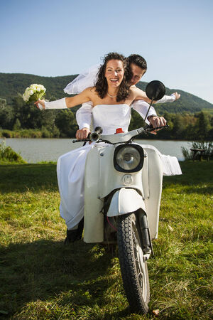 Happy wedding couple take a ride in a white motorcycle  photo