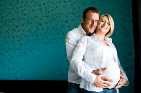 Portrait of a happy pregnant couple smiling for camera in front of a modern blue pattern wallpaper.  photo