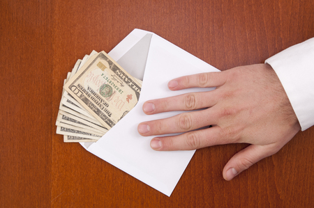Corruption concept. Business man take a stack of money in envelope.  photo