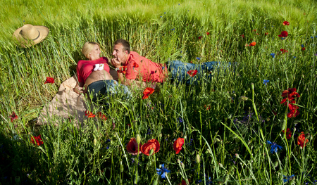 Portrait of a pregnant couple lying on blanket in a wheat field with poppy and straw hat. photo