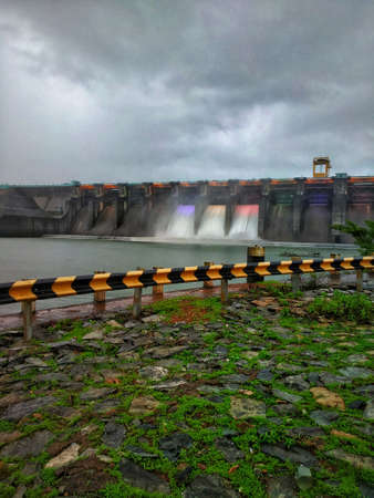 3 gates opened of the dam with colorful lights on the flowing water.