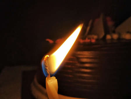 A Candle with a cake at the background for the birthday party.