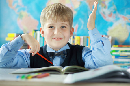 dreaminess: Portrait of smiling schoolboy drawing his hand in classroom at school