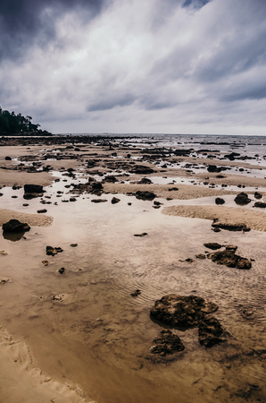 Low tide revealing stones on sandy coastline of Karon beach of Phuket island. Stock Photo